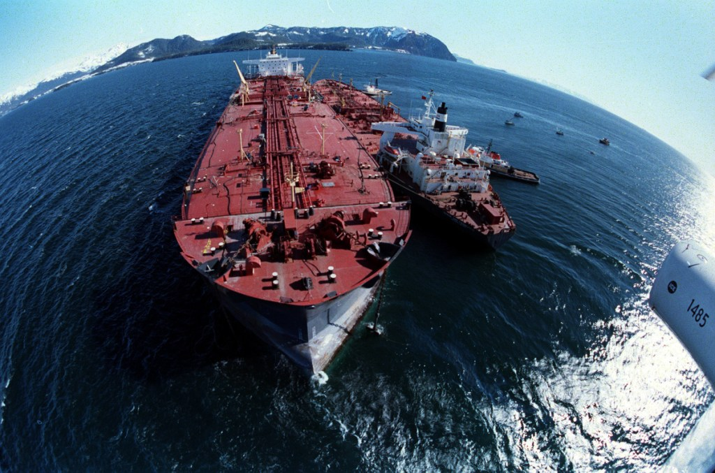 The grounded Exxon Valdez, left, unloads oil onto a smaller tanker in an effort to refloat the Valdez on April 4, 1989. The initial spill, on March 24, 1989,   let about 11 million gallons of crude oil gush into Prince William Sound.