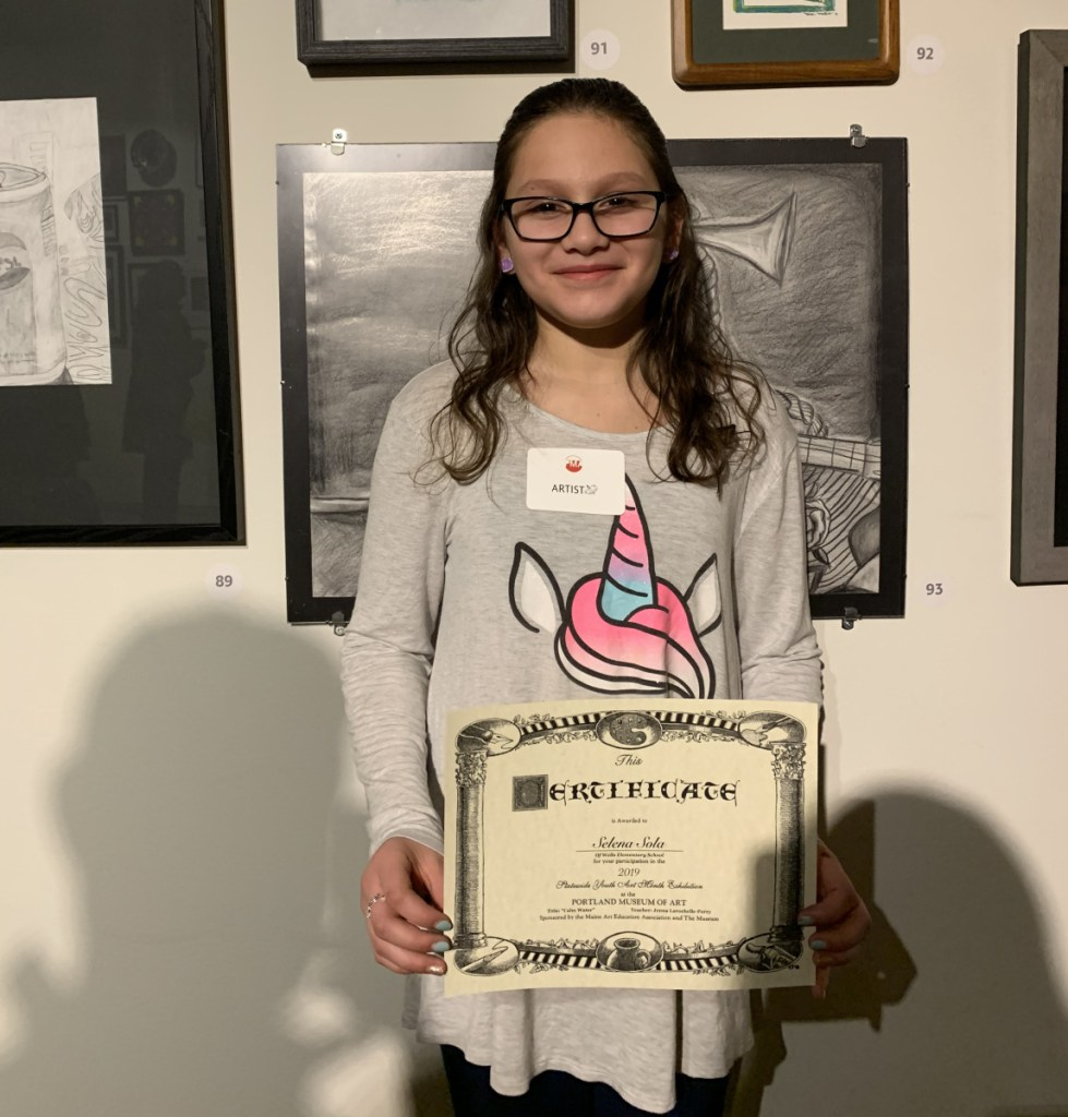 Wells fourth-grader Selena Sola poses next to her artwork on display at the Portland Museum of Art. She is one of three Wells-Ogunquit Community School District students selected to display their art.