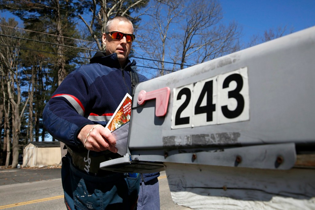 John Graham delivers mail Wednesday in Portland's North Deering neighborhood. Staffing shortages at the post office have caused delays in mail delivery for some residents in southern Maine.