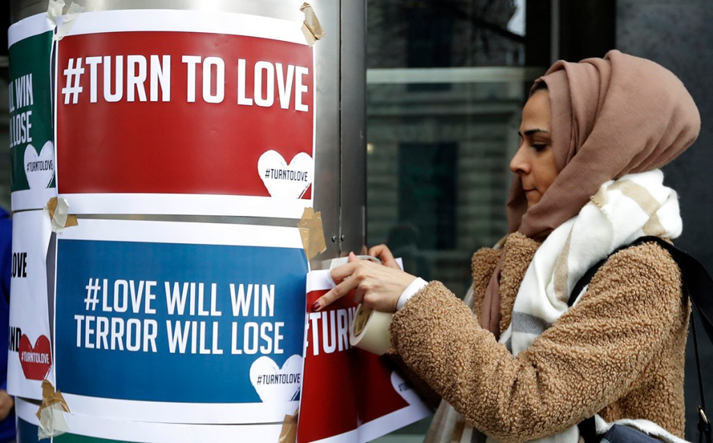 """A demonstrator hangs banners from multi-faith group 'Turn to Love' during a vigil at New Zealand House in London, Friday, March 15, 2019. Multiple people were killed in mass shootings at two mosques full of worshippers attending Friday prayers on what the prime minister called """"one of New Zealand's darkest days,"""" as authorities detained four people and defused explosive devices in what appeared to be a carefully planned attack."""