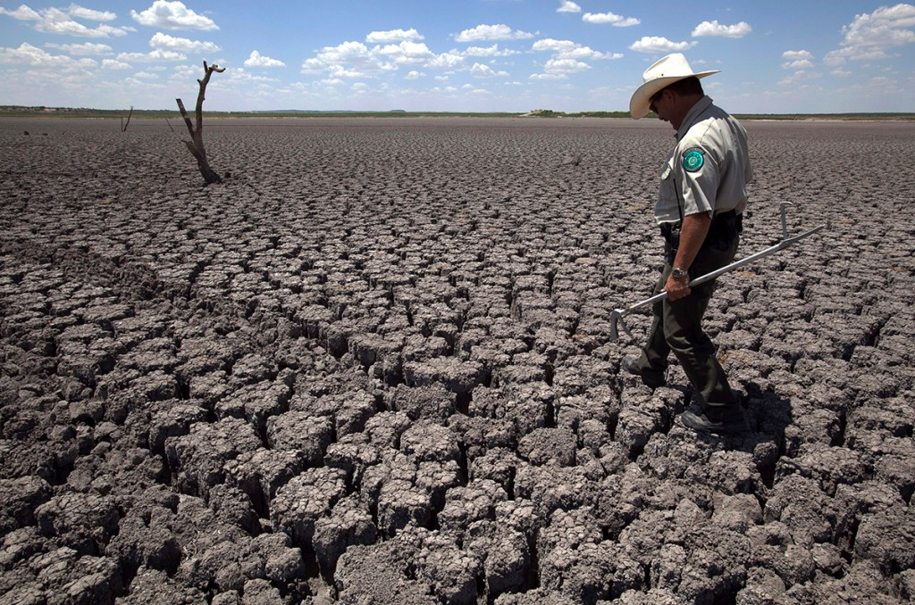 In this Aug 3, 2011 file photo, Texas State Park police officer Thomas Bigham walks across the cracked lake bed of O.C. Fisher Lake, in San Angelo, Texas. The impacts of record-breaking heat and years of low or no rainfall can be felt years after a dry spell passes.