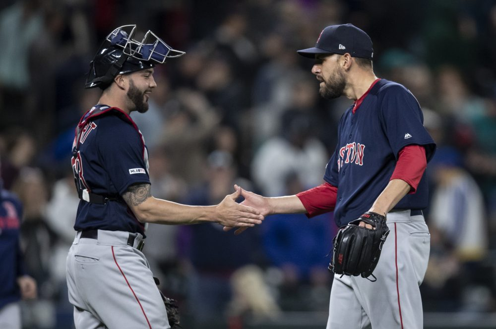 Red Sox pitcher Matt Barnes, right, shakes hands with catcher Blake Swihart after earning his first save of the season in Boston's 7-6 victory over the Mariners on Friday in Seattle.