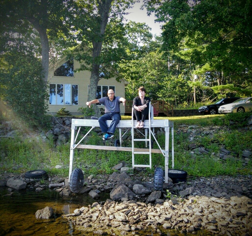 Robert Rubin and Cheryl Ayer sit on the dock at their Clary Lake property in Whitefield in August 2015, when the level in Clary Lake was more than 5 feet below the top of the Clary Lake dam.