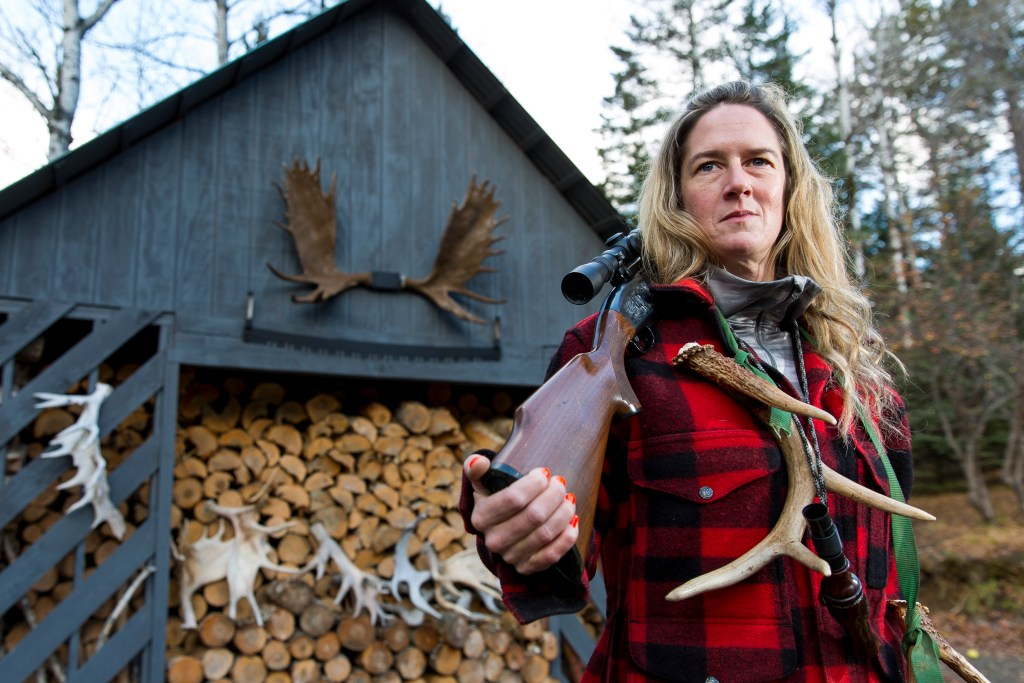 Liz Walker rests her Remington 7600 on her shoulder near a woodshed outside her Rangeley home.