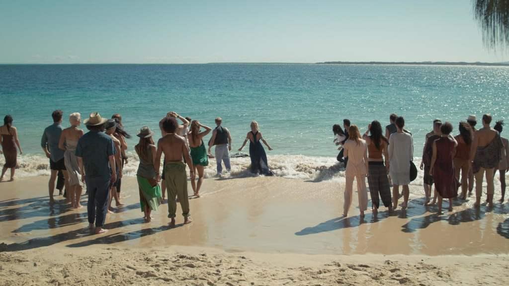 Scena z serialu Tidelands, grupa osób z osady pół-ludzi, pół-syren oczekująca na plaży na nadejście syren.