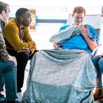 Yoss Inkl z synem na rękach w otoczeniu bohaterów Doktor Who