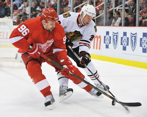 Redwings Tomas Holmstrom and Blackhawks Aaron Johnson battle in the corner for the puck in the first period. Daniel Mears / The Detroit News