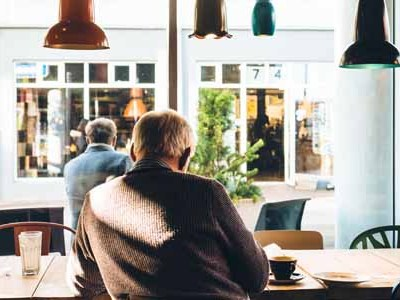 Older man sitting at a table in a coffee shop
