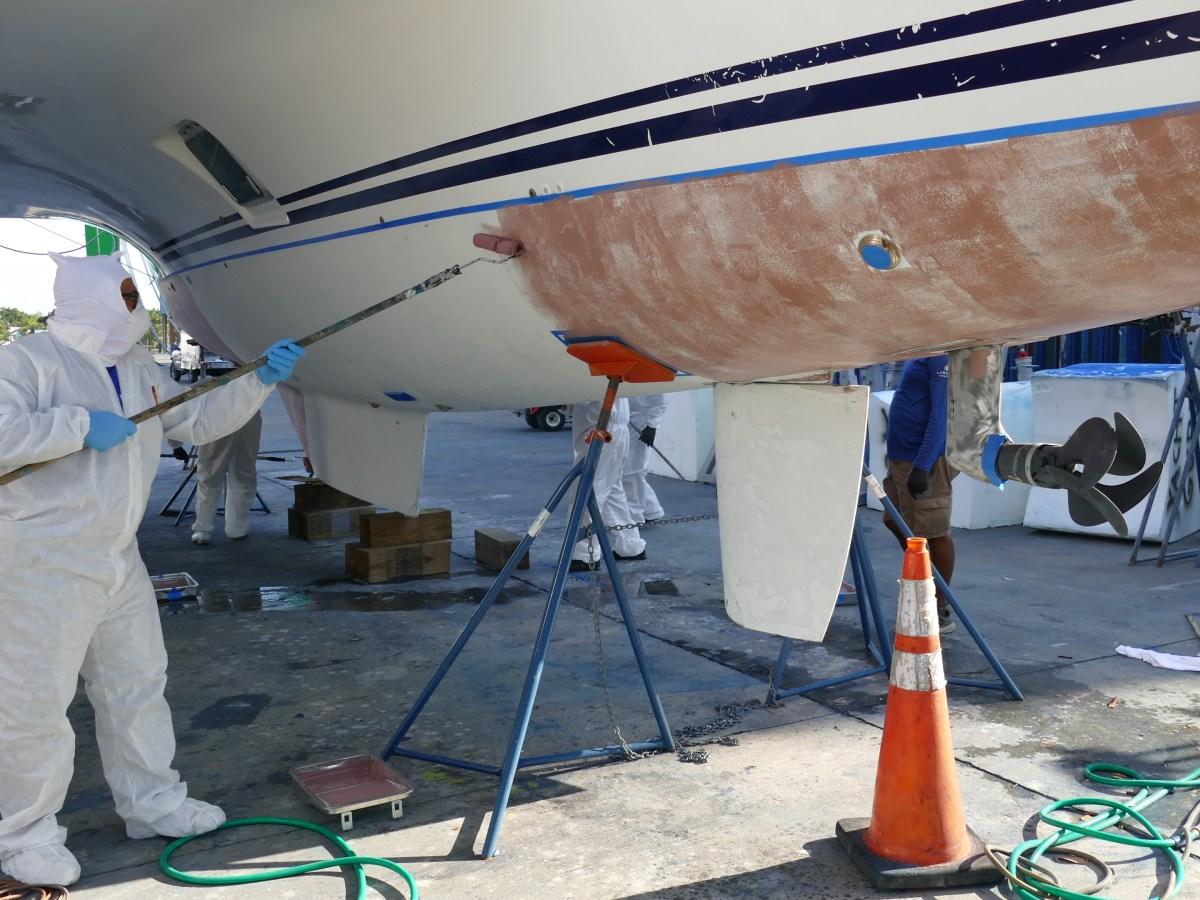 Multitech Marine Technician Painting Bottom Hull of Catamaran