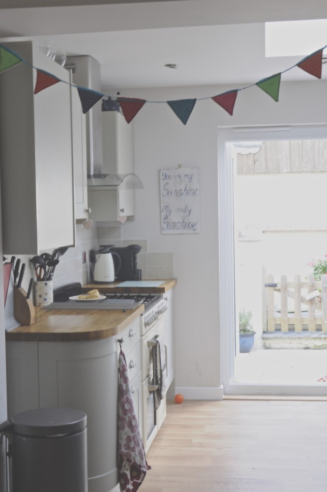 A modern country kitchen in sage green and cream with a focus range cooker