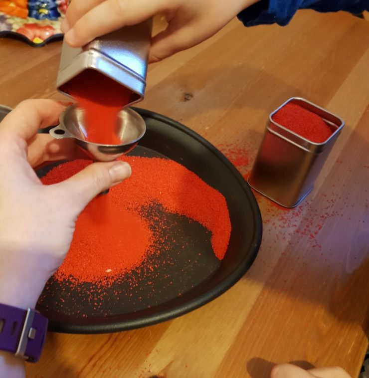 boy-playing-at-home-with-red-sand-kit-with-mum