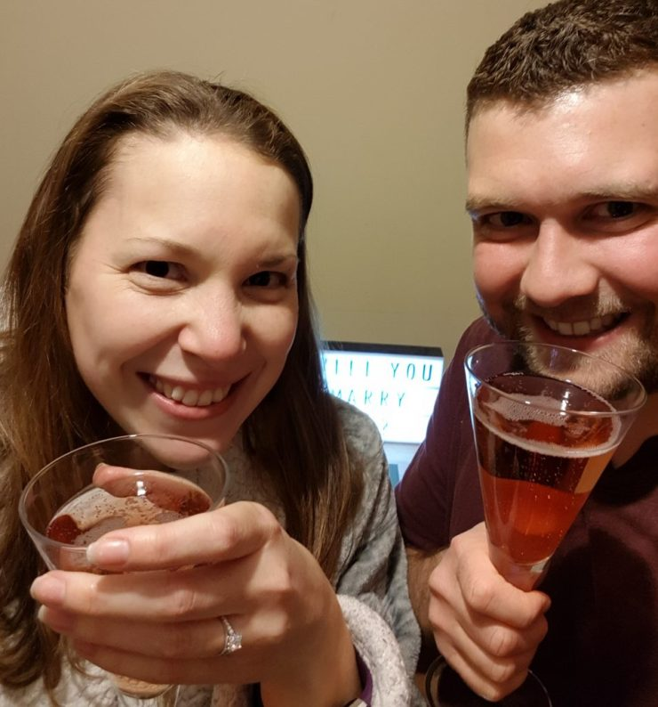 man-and-woman-celebrating-engagement-with-glasses-of-pink-champagne