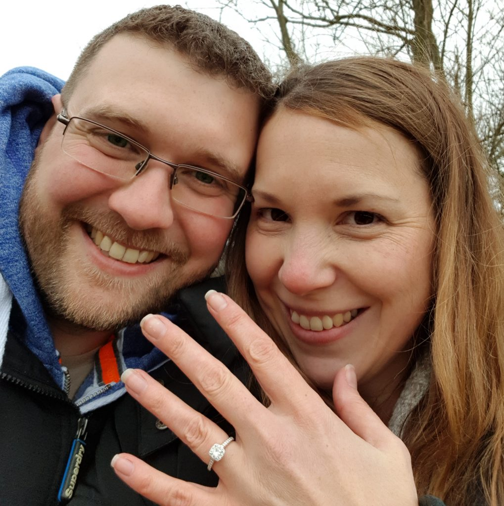 happy-couple-smiling-showing-off-engagement-ring