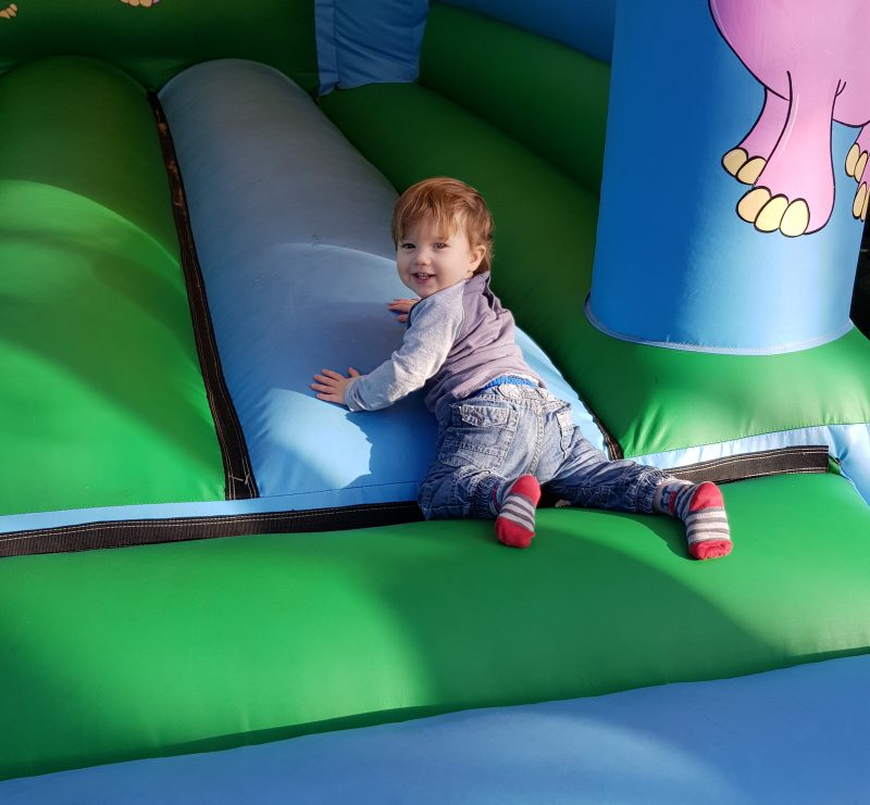 toddler-alone-on-bouncy-castle-smiling
