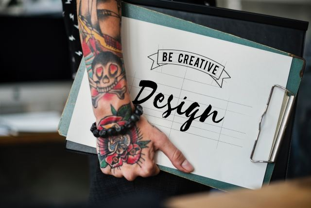 Tattooed arm holding a sketchbook that reads 'Be Creative - Design' Easy Ways to Earn Money From Home