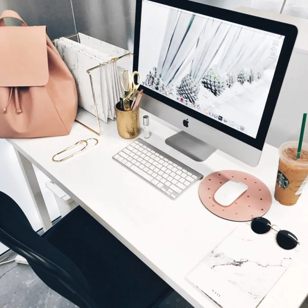 an apple mac on a desk along with a pink handbag, starbucks frappe, sunglasses and a giant paperclip. 2018 blog goals