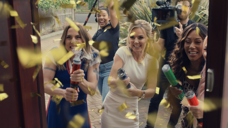 Spice girls and camera crew on someones doorstep pulling confetti poppers
