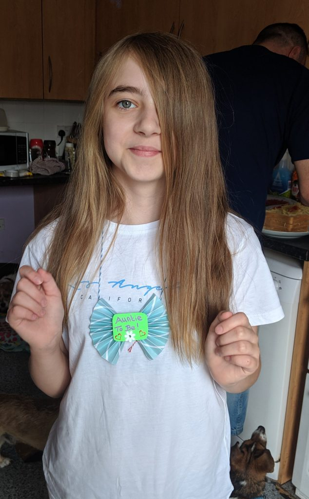 Young girl with long hair and a white t-shirt wearing a homemade baby shower badge which says 'Auntie to be'