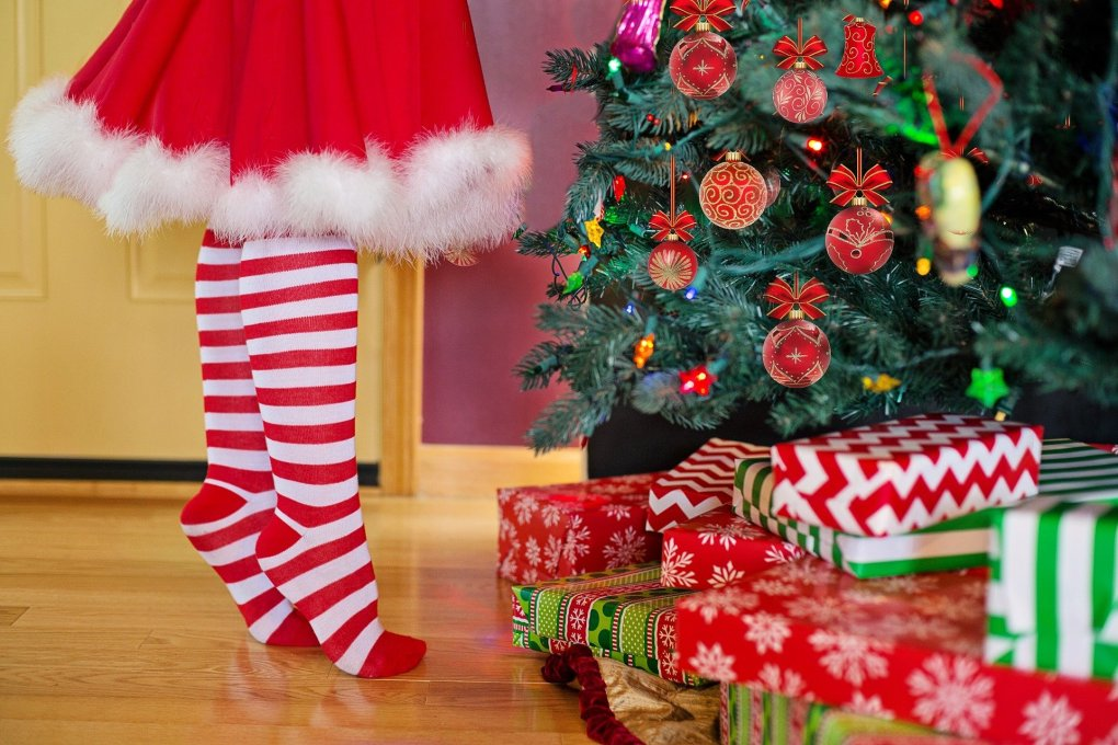 Childs feet in red and white stockings in front of a Christmas tree and presents