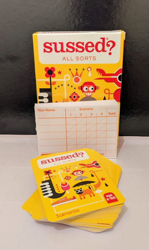 Sussed game box with the score sheet pad in front and then the game cards in front of that.