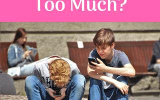 Two young boys sitting on some steps both staring at their mobile phones. Young girl in background also staring at her mobile phone