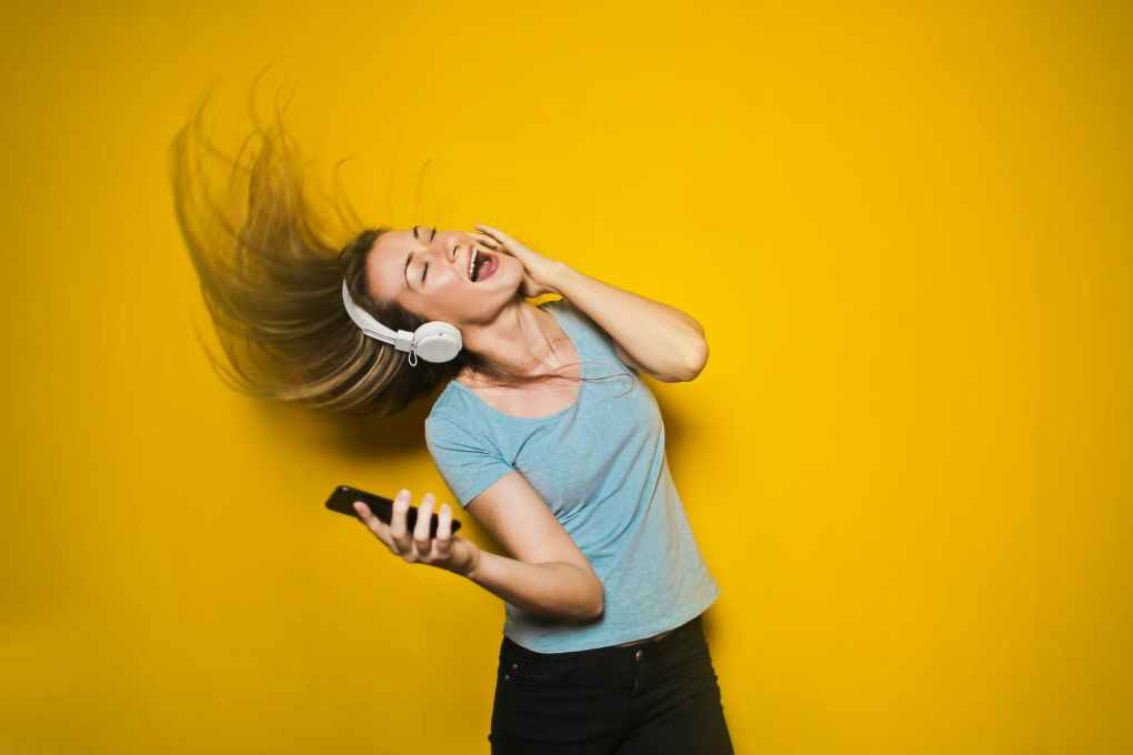 Lady dancing and singing with headphones on showing positivity
