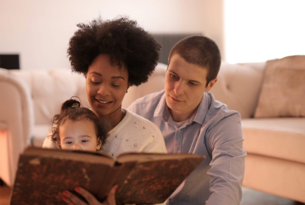 man, lady and child reading together at home as a family