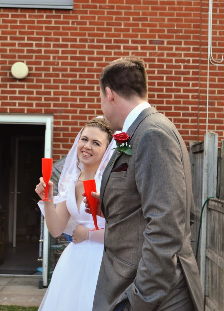Bride and groom making a toast at their COVID wedding holding red glasses