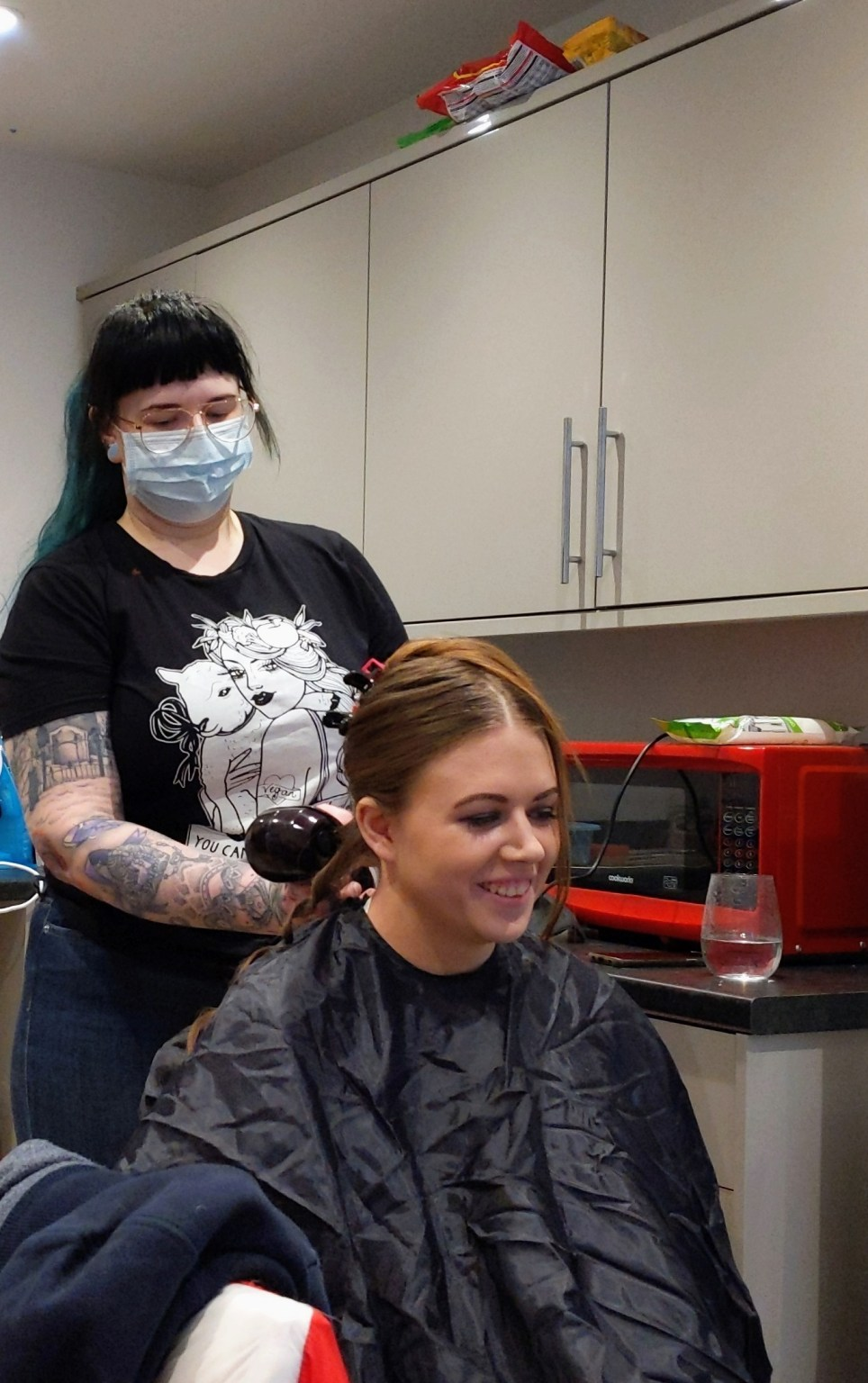 Hairdresser working on a bride to be, wearing a face mask. Getting ready for a COVID wedding