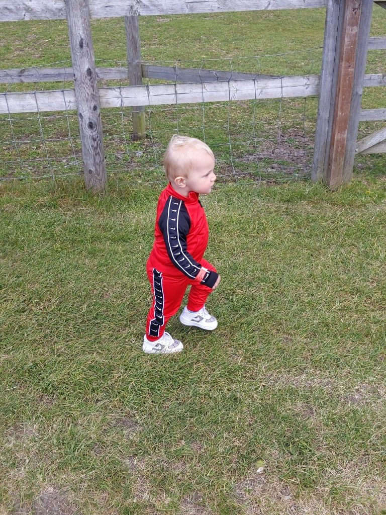 Keaton (male toddler) walking in a red and black tracksuit with white trainers