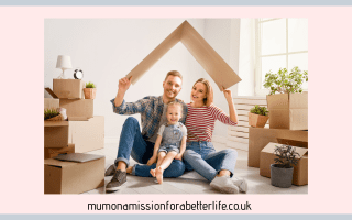 Family (man, woman, girl) sitting together in a room with moving boxes making a roof from a packing box over their heads