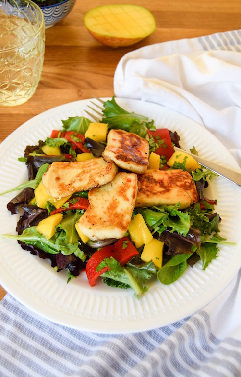 Halloumi cheese on top of a green salad on a plate with a fork