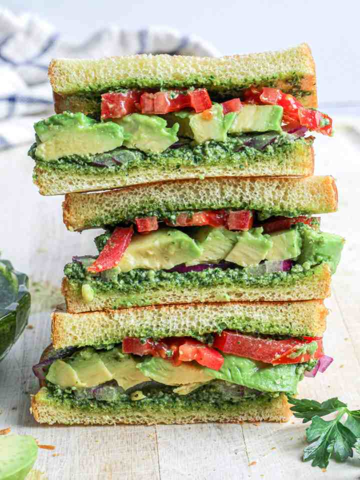 Avocado and Herb Pesto Sandwich with tomatoes, red onion and brioche bread.