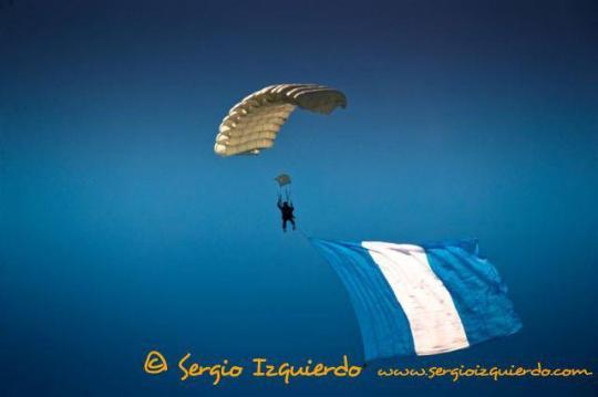 Paracaidista de la Fuerza Aérea Guatemalteca ondeando la bandera nacional. Sergio Izquierdo - El Origen de la Fuerza Aérea Guatemalteca FAG