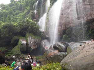 group of people sitting at the base of a waterfall eating lunch