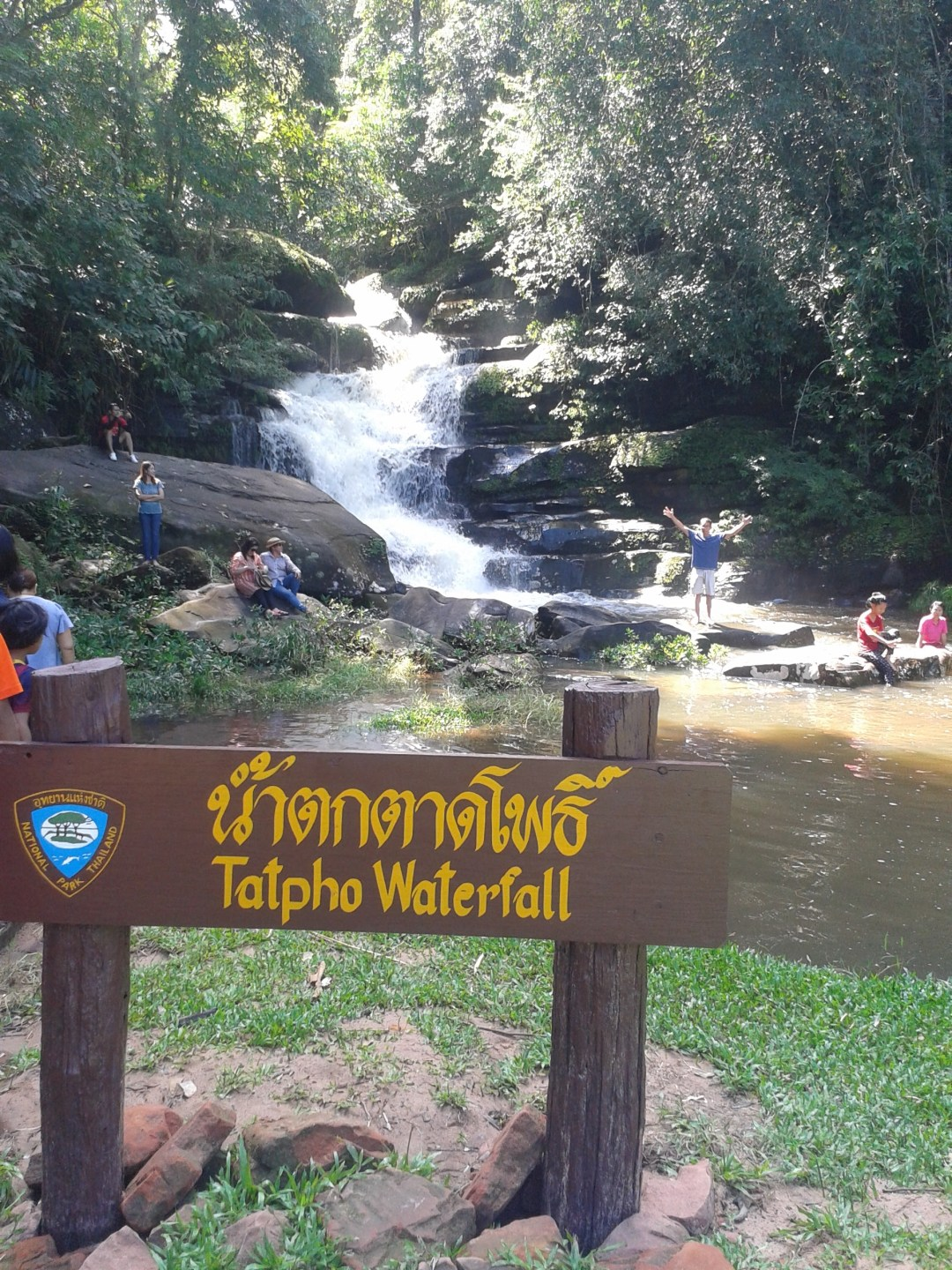 """sign in english and thai """"tatpho waterfall"""" and waterfall in background"""