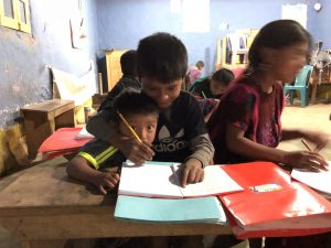 two students from CEMIK writing in their notebooks in a classroom