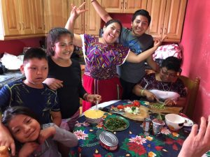 Brandon, one of our scholarship students, in Guatemala with his family in a kitchen