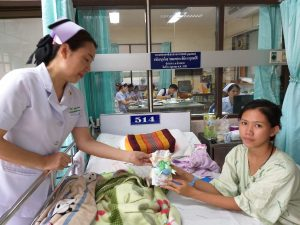 Thai nurse gives a new mom a bundle of baby clothes in the hospital