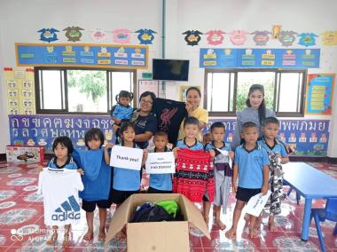 local partners lokgatat giving clothes to school kids, all pose with shirts and thank you sign for a photo
