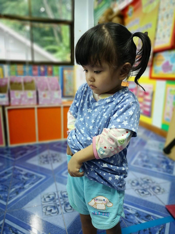 little girl tucks her blue shirt into her shorts