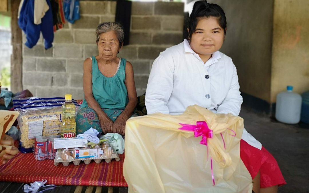 Nang Wanni sits on a mat with Fon as they look at care packages