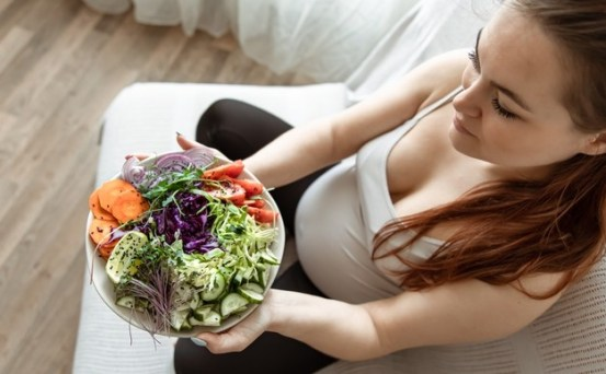pregnant-woman-with-plate-fresh-vegetable-salad-home-couch-top-view_169016-10998