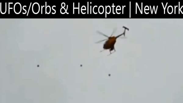Orbes negros volando cerca de un helicóptero sobre Marcy, NY 16-Oct-2020