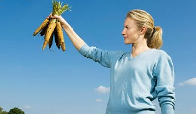 Woman-holding-carrots-fresh-from-ground.jpg
