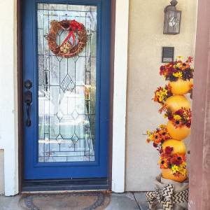 porch with Autumn pumpkin totem with silk flowers
