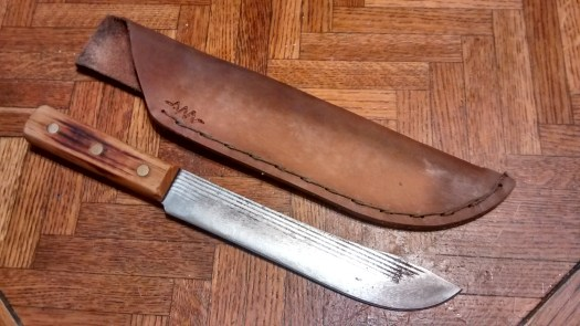 a large knife on a wooden table, next to a handmade leather sheath