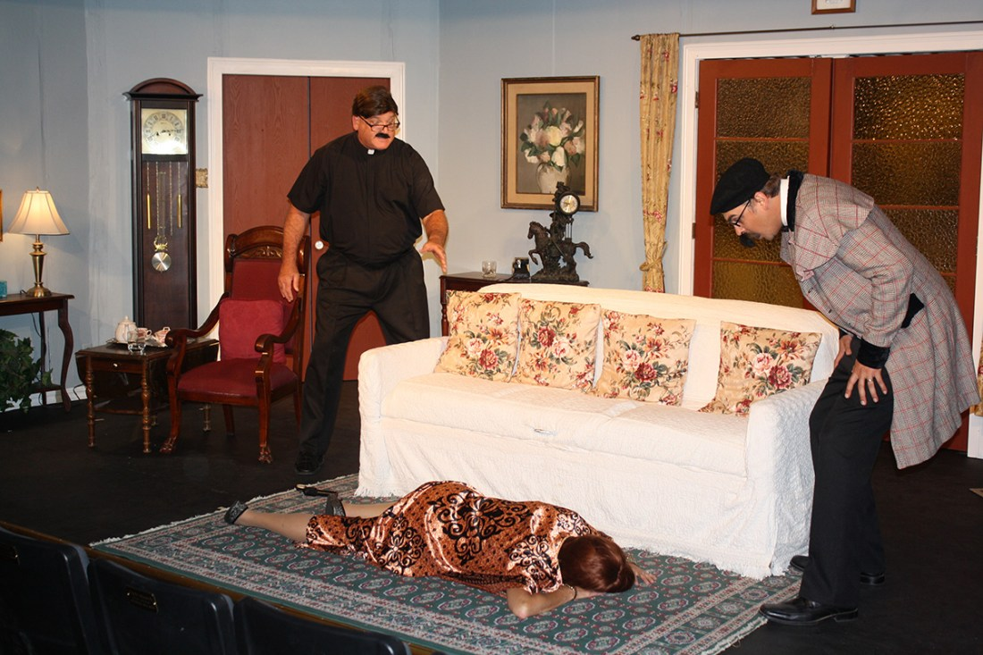 Photograph of man dressed as a priest, a dead body on the floor and a surprised inspector in the in the Kings Players production of 'Murder Me, Murder Me Not.' Photos / Kings Players