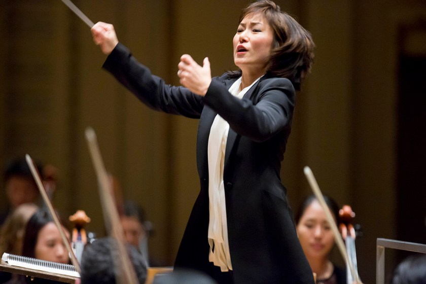 Photograph of Rei Hotoda with arms outraised conducting an orchestra.