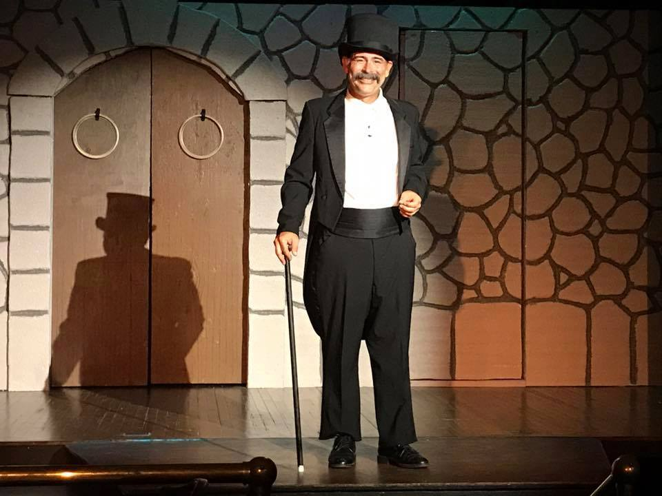 Dr. Frankenstein, played by Eric Bailey, standing on stage with top hat and cane.